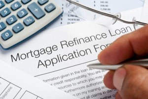 Mortgage Refinance Application Form with pen, calculator, writin